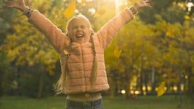 Vrolijk meisje die de herfstbladeren werpen, genietend dalings van seizoen, die gelukkige pret hebben, stock videobeelden