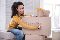 Vrolijk meisje die doos met bezittingen voor huisbureau ondertekenen stock foto