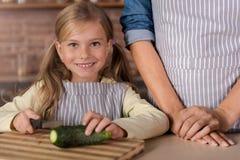 Vrolijk meisje die een komkommer in de keuken snijden royalty-vrije stock fotografie