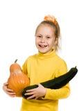 Vrolijk meisje die een pompoen en een pompoen houden Royalty-vrije Stock Foto