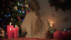 Vrolijk meisje die Kerstmis huidig onder fonkelende boom plaatsen, die verrassing voorbereiden stock footage