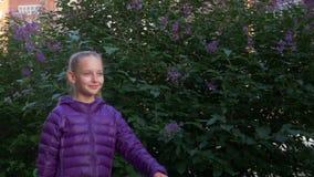 Vrolijk meisje die langs bloeiende lilac bomen in de lentestad lopen met skateboard in handen Gelukkig tienermeisje stock videobeelden