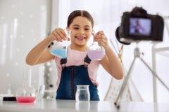 Vrolijk meisje die twee chemische flessen op camera tonen Stock Fotografie
