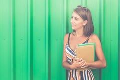 Vrolijk meisje met boeken tegen groene muur in openlucht royalty-vrije stock fotografie