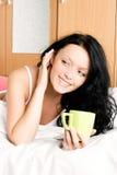 Vrolijk meisje met een kop van koffie in bed Royalty-vrije Stock Afbeelding