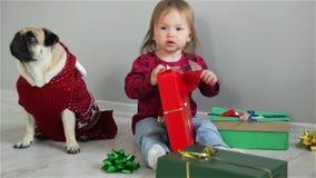 Vrolijk meisje met een richtende glimlachzitting op de vloer met giften die van Kerstmis met familiehond het dragen genieten stock footage