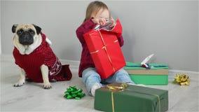Vrolijk meisje met een richtende glimlachzitting op de vloer met giften die van Kerstmis met familiehond het dragen genieten stock video