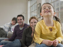 Vrolijk Meisje met Familiezitting op Bank Royalty-vrije Stock Fotografie