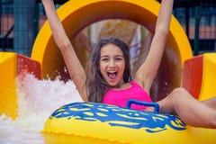 Vrolijk meisje met handen die omhoog pret hebben die binnen waterpark op opblaasbare ring glijden royalty-vrije stock foto