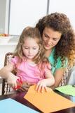 Vrolijk meisje scherp document met moeder bij de lijst Stock Foto