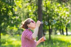 Vrolijk mooi donkerbruin meisje in glazen die zeepbels blazen Stock Foto
