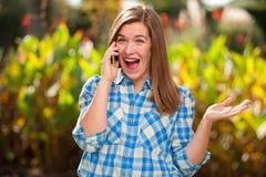 Vrolijk mooi jong meisje die op de telefoon spreken stock foto's