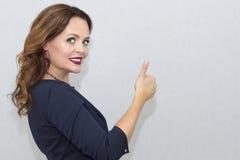 Vrolijk mooi meisje die duimen over grijze achtergrond tonen het bekijken camera Stock Afbeelding