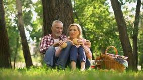 Vrolijk oud paar die op gras rusten en burgers, romantische datum in park eten stock videobeelden