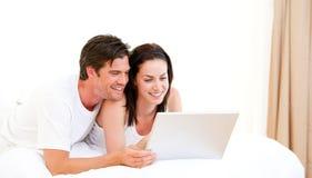 Vrolijk paar dat een computer met behulp van stock afbeelding