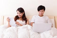 Vrolijk paar die aanrakingsstootkussen in bed gebruiken Royalty-vrije Stock Afbeelding