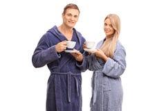 Vrolijk paar die in badjassen koffie drinken stock foto's