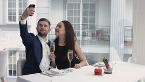 Vrolijk paar die een humoristische selfie met een smartphone nemen bij het restaurant stock video