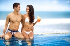 Vrolijk paar die van volgende zwembad genieten royalty-vrije stock foto