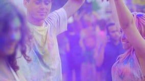 Vrolijk paar die zich aan muziek in menigte bij partij, gekleurd die poeder bewegen in lucht wordt bespoten stock footage
