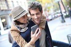 Vrolijk paar met smartphone in stadsstraat stock afbeeldingen