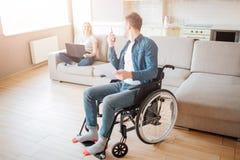 Vrolijk paar in ruimte samen De jonge man met inclusiviteit zit op rolstoel en kijkt terug op vrouw De telefoon van de holding stock fotografie