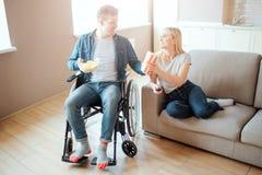 Vrolijk paar samen in ruimte De kerel met onbekwaamheid zit op wheelchaor en bekijkt vrouw Zij zit op bank en glimlach aan stock afbeeldingen