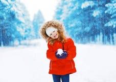 Vrolijk positief kind met sneeuwbal die pret hebben in openlucht royalty-vrije stock afbeeldingen