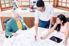 Vrolijk professioneel team die aan een innovatief project werken stock foto's