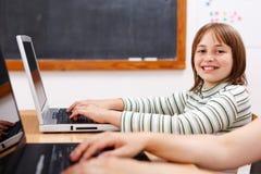 Vrolijk schoolmeisje met laptop Stock Afbeeldingen