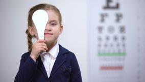 Vrolijk schoolmeisje sluitend oog, die visie in oftalmologische kliniek controleren stock video