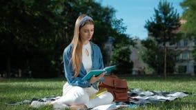 Vrolijk studentenmeisje die haar nota's bestuderen Jonge vrouwenzitting op het gras in het park, holding een open notitieboekje stock footage