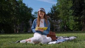 Vrolijk studentenmeisje die haar nota's bestuderen Jonge vrouwenzitting op het gras in het park, holding een open notitieboekje stock videobeelden
