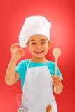 Vrolijk weinig chef-kok die goede smaak toont Stock Foto