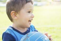 Vrolijk weinig jongen die in openlucht met een bal spelen stock foto