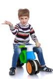 Vrolijk weinig jongen in een gestreept sweater en een blauw royalty-vrije stock afbeelding