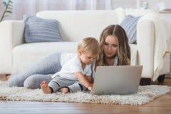 Vrolijk weinig jongen en zijn moeder die op de vloer liggen terwijl het spelen van spel op laptop Royalty-vrije Stock Foto