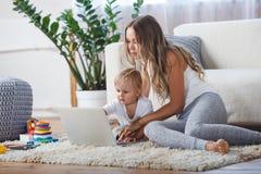 Vrolijk weinig jongen en zijn moeder die op de vloer liggen terwijl het spelen van spel op laptop Stock Foto