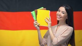 Vrolijk wijfje die voorbeeldenboeken tegen Duitse vlag, vreemde taalcursussen tonen stock footage
