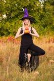 Vrolijk wijfje in heksenkostuum het praktizeren yoga Royalty-vrije Stock Afbeeldingen