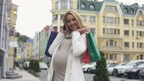 Vrolijk zwanger wijfje die, houdend het winkelen zakken en smartphone in camera glimlachen stock footage