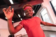 Vrolijke aandachtige jonge danser die zijn handen opheffen tijdens uitvoerders stock afbeelding