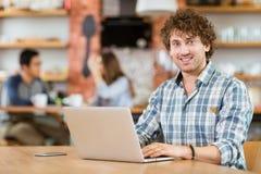 Vrolijke aantrekkelijke jonge krullende mens die laptop in koffie met behulp van Royalty-vrije Stock Foto