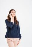 Vrolijke aantrekkelijke jonge vrouw die en zich op celtelefoon bevinden spreken Royalty-vrije Stock Afbeeldingen