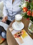 Vrolijke aantrekkelijke jonge vrouw die latte en laptop in koffie met behulp van drinken royalty-vrije stock foto