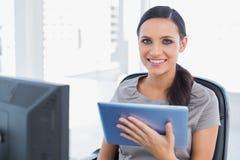 Vrolijke aantrekkelijke secretaresse die tabletpc met behulp van Stock Foto's