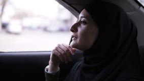 Vrolijke, aantrekkelijke vrouw die in zwarte hijab hoofdsjaal venster in auto bekijken Glimlachende vrouw die van haar manier, de stock video
