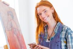 Vrolijke aantrekkelijke vrouwenschilder die aan muziek van mobiele telefoon luisteren Royalty-vrije Stock Afbeelding