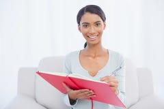 Vrolijke aantrekkelijke vrouwenzitting bij het comfortabele bank schrijven Stock Afbeeldingen
