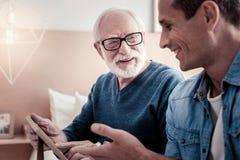 Vrolijke aardige mens die aan zijn grootvader spreken royalty-vrije stock afbeelding